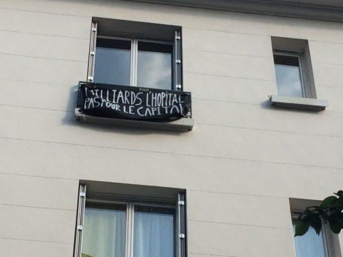 photographie d'une banderole noire à une fenêtre : des milliards pour l'hôpital, pas pour le capital