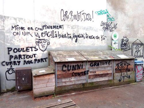"""photographie d'une ruelle, containers à poubelle en bois et nombreux graffitis : """"Coro, boulot, dodo"""", """"même en confinement, on nik la bac"""", """"liberté, égalité, trace de ké"""", poulets partout, curry nulle part"""" et """"cunni gratuite contre..."""""""