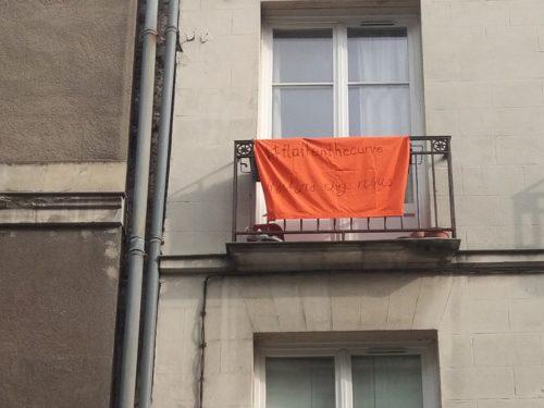 Photographie d'un balcon, banderole orange : #flattenthecurve, restons chez  nous
