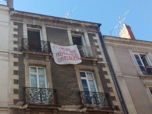 """photographie d'une facade d'immeuble. Au deuxième étage, une banderole entre deux balcons : """"préparons les luttes de demain"""""""
