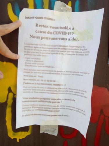 Affichette scotchée sur un mur : bonjour voisins et voisines, Restez vous isolé.e.s à cause fu COVID-19 ? nous pouvons vous aider