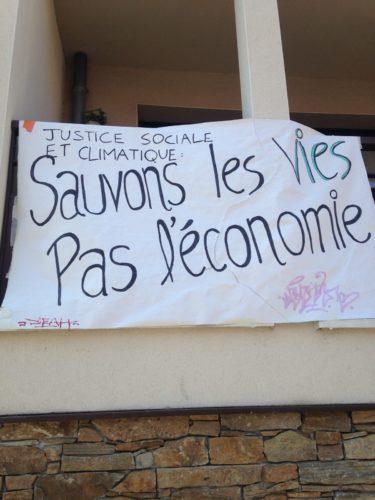 photographie d'une banderole : justice sociale et climatique : sauvons les vies, pas l'économie