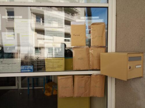 photographie d'une baie vitrée et d'une boîte aux lettres ; sur la vitre sont scotchées 7 enveloppes kraft portant des prénoms