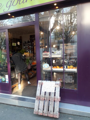photographie d'une devanture de magasin de typé épicerie, devant laquelle une palette de bois est posée, sur laquelle une affiche est fixée