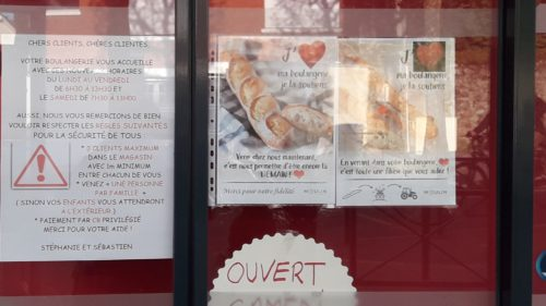 Photographie d'une devanture de boulangerie. Sur la vitrine, une affiche indiquant les horaires d'ouverture et les mesures de précaution
