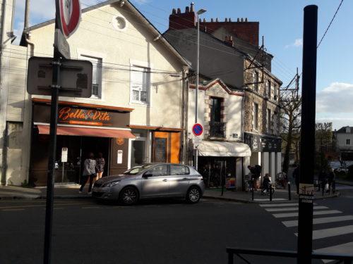"""Phorgraphie d'une rue, quelques passants, une devanture de magasin """"Bella Vita"""", une voiture grise, un passage piéton, un poteau avec une affichette"""