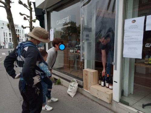 Photographie d'une devanture de caviste. 3 personnes sont visibles : le commerçant, et deux passants dont l'un porte un bébé ; ils sont en train de lire l'affiche posée sur la devanture