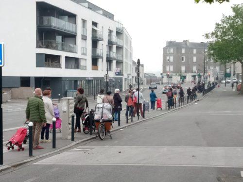 photographie d'une longue file d'attente dans la rue. Plus d'une vingtaine de personnes, portant pour certaines des caddies, sont visibles de dos