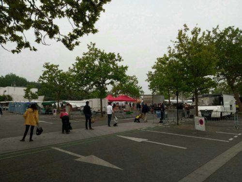 Photographie d'une place de marché ; on voit des camions, des auvents et des clients faisant la queue devant un vigile ; l'entrée dans le marché est limitée par des ganivelles