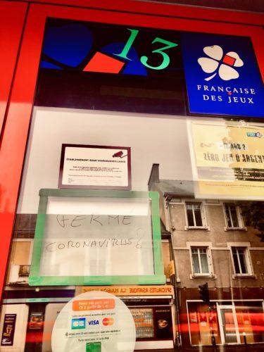 """Devanture d'un bureau de tabac présenant plusieurs affichettes (française des jeux, vidéosurveillance, cartes bancaires) et et l'inscription """"FERME CORONAVIRUS ?"""""""