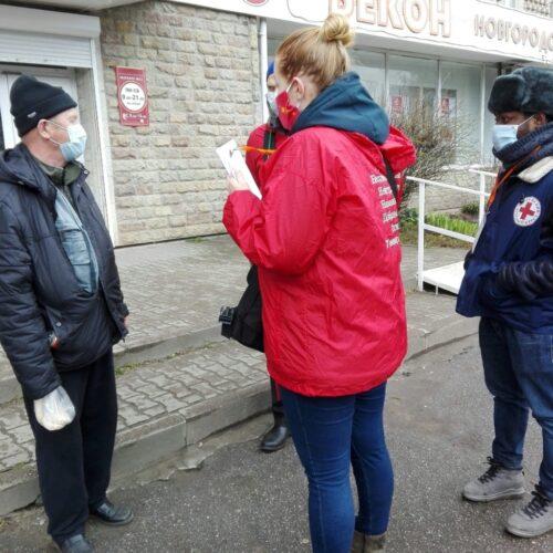 Photographie de 4 personnes : 3 bénévoles (dont une femme) de la Croix rouge s'adressant à un homme âgé ; tous les personnages portent un masque