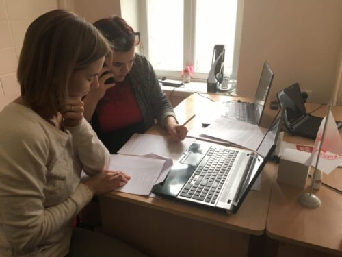 Photographie présentant 2 femmes travaillant devant un ordinateur portable ; l'une est au téléphone et prend des notes, l'autre lit un document papier